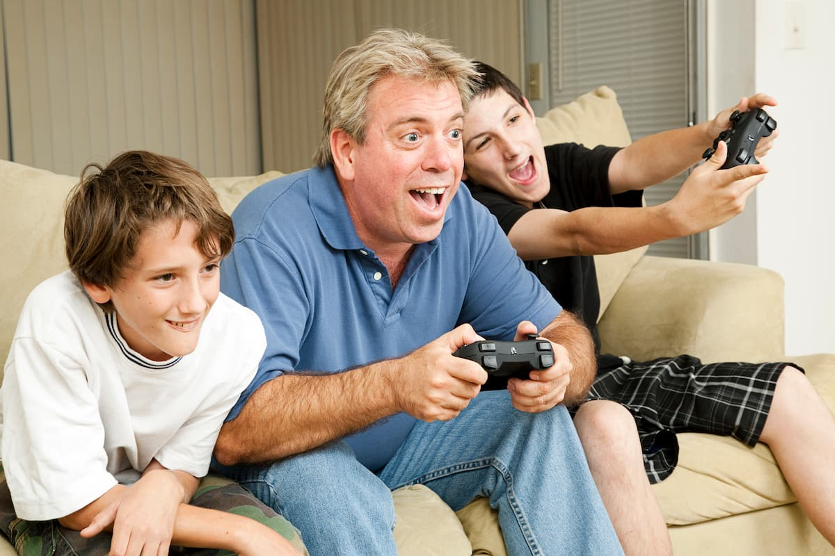 Father and sons playing video games on the couch