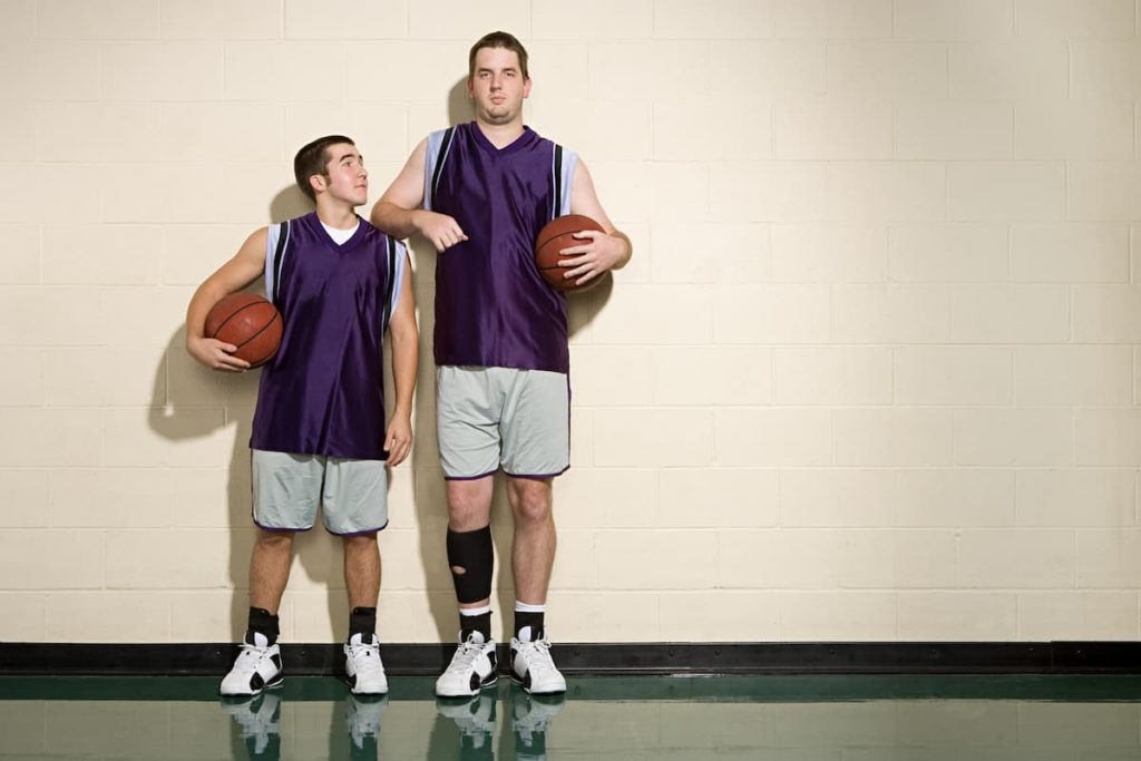 Father standing taller next to his son on the basketball court with son wondering if he can grow taller than his dad
