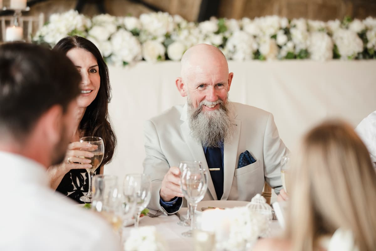 Father, who is best man at a wedding, sitting down at table socialising
