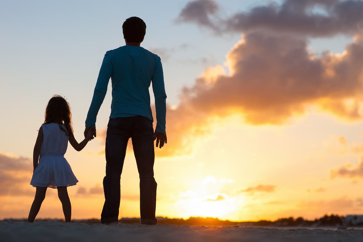 father and daughter holding hands at sunset