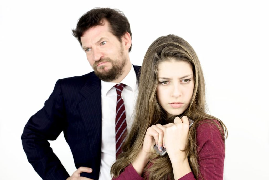 Angry father looking off to the side with upset daughter in front of him