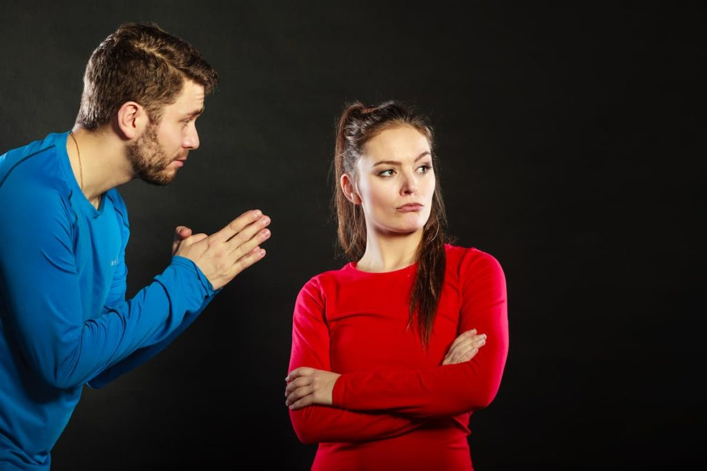 Angry wife looking the other direction from pleading husband next to her